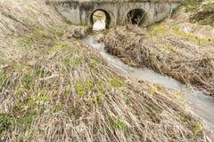 Wiosna przepływ woda w łóżku mała rzeka przechodzi przez wielkich drenażowych drymb pod masa mostem Zdjęcia Royalty Free