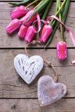 Wiosna tulipany i dwa dekoracyjnego serca na rocznika drewnianym backg Obrazy Royalty Free