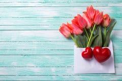 Wiosna tulipany w biały kopertowym i dwa serca na turkusowym pai Zdjęcia Stock