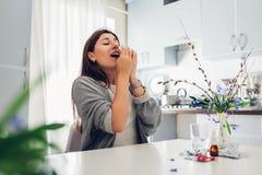 Wiosny alergia Młodej kobiety kichnięcie przez kwiatów otaczających z pigułkami na kuchni Sezonowy alergii pojęcie zdjęcie stock