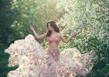 Wiosny dziewczyna z falistego włosy tanem na tle kwiatonośni drzewa Jest ubranym różową suknię która trzepocze z kwiatami zdjęcie stock