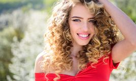 Wiosny dziewczyna z kędzierzawego włosy ono uśmiecha się Piękno włosiany salon Piękno dziewczyna z długim i błyszczącym kędzierza zdjęcie stock