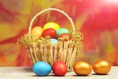 Wiosny Easter wakacje, kolorowi jajka i złoty jajko w koszu, Obraz Royalty Free