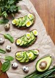 Wiosny jedzenie Cała zbożowa chlebowa grzanka ściska z avocado, szpinaka, guacamole, arugula i przepiórki jajkami na pergaminie, Fotografia Stock