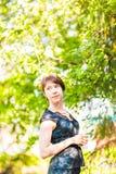 Wiosny kobieta w lato sukni odprowadzeniu w zieleń parku cieszy się słońce Figlarnie i piękna mieszana biegowa dziewczyna na ciep Zdjęcia Stock