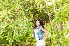 Wiosny kobieta w lato sukni odprowadzeniu w zieleń parku cieszy się słońce Figlarnie i piękna mieszana biegowa dziewczyna na ciep Fotografia Stock