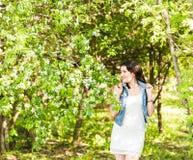 Wiosny kobieta w lato sukni odprowadzeniu w zieleń parku cieszy się słońce Figlarnie i piękna mieszana biegowa dziewczyna na ciep Obraz Stock