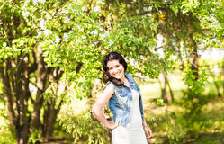 Wiosny kobieta w lato sukni odprowadzeniu w zieleń parku cieszy się słońce Figlarnie i piękna mieszana biegowa dziewczyna na ciep Fotografia Royalty Free