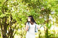 Wiosny kobieta w lato sukni odprowadzeniu w zieleń parku cieszy się słońce Figlarnie i piękna mieszana biegowa dziewczyna na ciep Zdjęcie Royalty Free