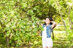 Wiosny kobieta w lato sukni odprowadzeniu w zieleń parku cieszy się słońce Figlarnie i piękna mieszana biegowa dziewczyna na ciep Obrazy Royalty Free