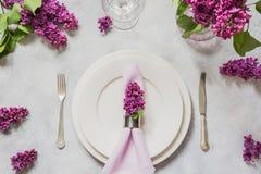 Wiosny miejsca stołowy położenie z bzem kwitnie, silverware na światło stole Odgórny widok zdjęcia stock