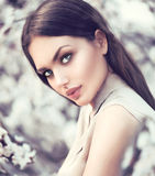Wiosny mody dziewczyna outdoors w kwitnących drzewach Zdjęcie Royalty Free