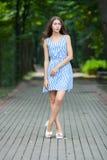 Wiosny piękna kobieta w lato sukni odprowadzeniu w zieleń parkowym cieszy się weekendzie Figlarnie i piękna caucasian dziewczyna  zdjęcia royalty free
