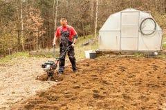 Wiosny przygotowania ziemia dla sia? z tiller Wiosny praca w ogr?dzie Rolnik orze ziemi? z kultywatorem, przygotowywa je fotografia royalty free