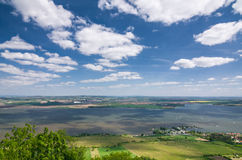 Wiosny wieś z jeziorem, polami i niebieskim niebem z chmurami, Obrazy Stock