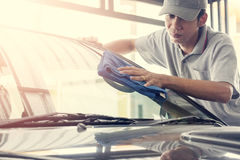 Wipe the car glass with microfiber cloth. Auto service staff in grey uniform wipe the car glass with microfiber cloth-car detailing and valet concepts Stock Photos