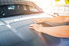 A wipe clean the car with cloth and polishing waxing cream. Vintage tone royalty free stock photo