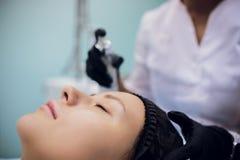 Wipe med den sterila servettframsidan Ung kvinna som mottar behandlingar i skönhetsalonger arkivfoton