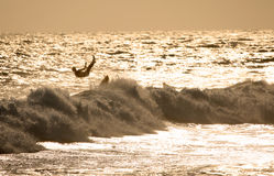 Wipe out. Silhouette of a surfer at sunset wiping out Stock Photo