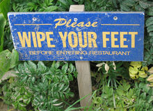 Wipe your feet sign. A blue sign asking patrons to wipe their feet Stock Photo