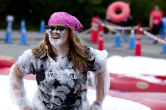 Wipeout 5K Run obstacles course - Foam of Fury. Woman covered in foam at the Foam of Fury obstacle at the Wipeout 5K Run obstacles course in Wilmington, Delaware royalty free stock image