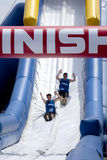 Wipeout 5K Run obstacles course - happy endings. Friends sliding happy endings waterslide obstacle at the finish of the Wipeout 5K Run obstacles course in royalty free stock photo