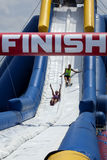 Wipeout 5K Run obstacles course - happy endings. Friends sliding happy endings waterslide obstacle at the finish of the Wipeout 5K Run obstacles course in stock image