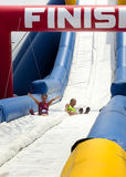Wipeout 5K Run obstacles course - happy endings. Friends sliding happy endings waterslide obstacle at the finish of the Wipeout 5K Run obstacles course in royalty free stock photos