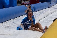 Wipeout 5K Run obstacles course - happy endings. Friends sliding happy endings waterslide obstacle at the finish of the Wipeout 5K Run obstacles course in royalty free stock images