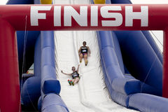 Wipeout 5K Run obstacles course - happy endings. Friends sliding happy endings waterslide obstacle at the finish of the Wipeout 5K Run obstacles course in royalty free stock image