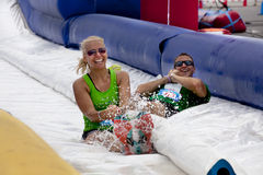 Wipeout 5K Run obstacles course - happy endings. Friends sliding happy endings waterslide obstacle at the finish of the Wipeout 5K Run obstacles course in royalty free stock photography