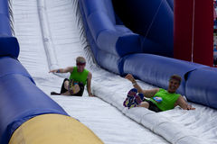 Wipeout 5K Run obstacles course - happy endings. Friends sliding happy endings waterslide obstacle at the finish of the Wipeout 5K Run obstacles course in stock photo
