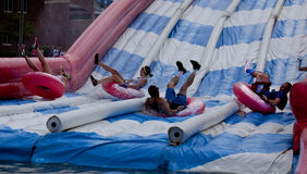 Wipeout 5K Run obstacles course - tumble tubes. Woman splashes into the bottom of the tumble tubes, water slide obstacle at the Wipeout 5K Run obstacles course stock photography