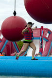 Wipeout 5K Run obstacles course - wrecking balls. Woman running at the wrecking balls water obstacle at the Wipeout 5K Run obstacles course in Wilmington royalty free stock images