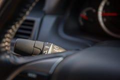 Wiper control stem between gauge mile and steering wheel. Wiper control stem between gauge mile, dashboard, and steering wheel in luxury car Stock Photo
