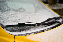 Wiper and windscreen of the parked car covered with snow. Close-up. Royalty Free Stock Images