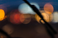 Wiper on windshield and traffic lights. A wiper on a windshield and blurred traffic lights Stock Image