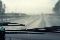 Wipers clean the windshield of the car from rain drops. View from inside the car.  stock photos