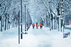 Wipers in orange vests are walking along a snowy alley stock photo