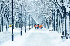 Wipers in orange vests are walking along a snowy alley stock photos