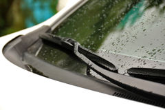 Wipers on windshield of car close up on rainy day Stock Photo