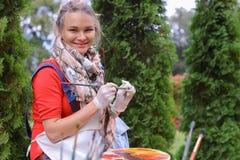 Wipes девушки чистят щеткой и кладут в банк, смотря изображение которые стоят Стоковые Фото