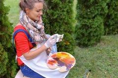 Wipes девушки чистят щеткой и кладут в банк, смотря изображение которые стоят Стоковое фото RF