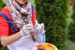 Wipes девушки чистят щеткой и кладут в банк, смотря изображение которые стоят Стоковое Изображение RF