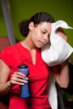 Wiping away the sweat. Attractive young girl in the gym wiping away the sweat stock photography