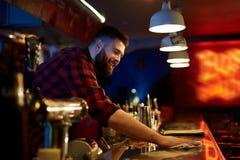 Wiping bar counter. Bearded barman wiping bar counter Royalty Free Stock Images
