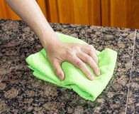 Wiping down Kitchen Stone Countertop Stock Photos