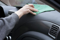 Wiping Dust In Car. Driver hand wiping the dust from a car windscreen and dashboard Stock Photo