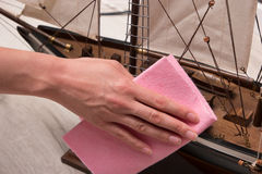 Wiping the dust from wooden sailing ship. Royalty Free Stock Image