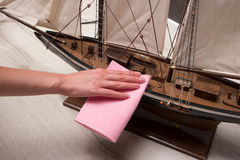 Wiping the dust from the wooden ship. Stock Images